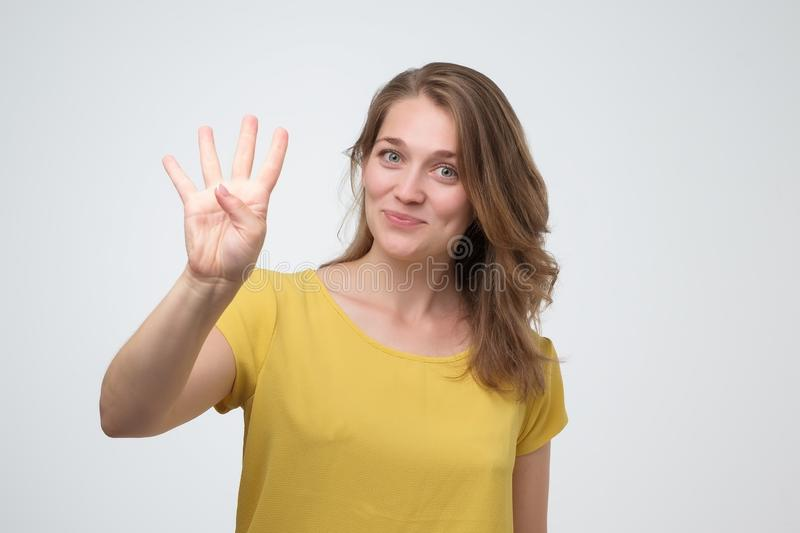 Pretty caucasian young woman holding up four fingers. You have several options concept royalty free stock photo