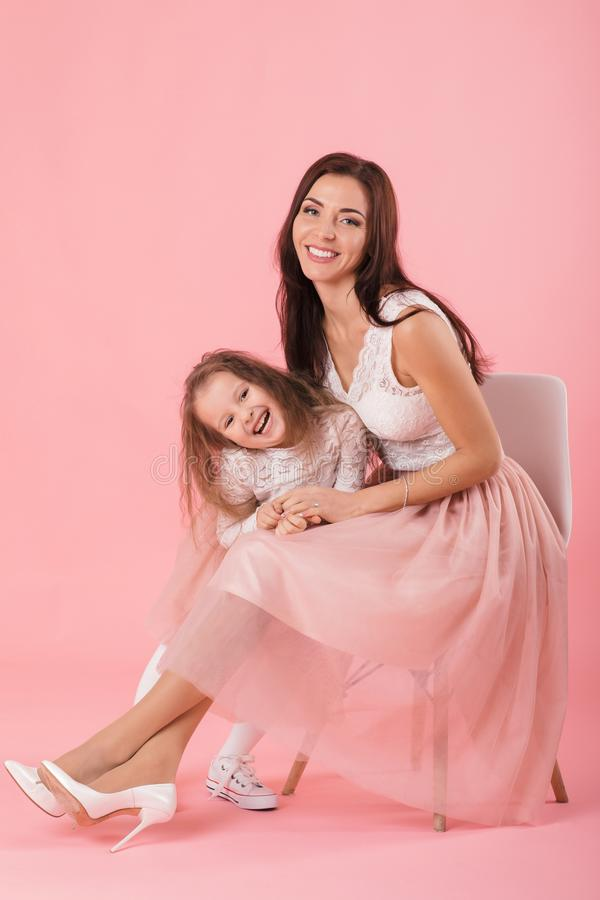 Charming mother and smiling daughter on pink background royalty free stock photos