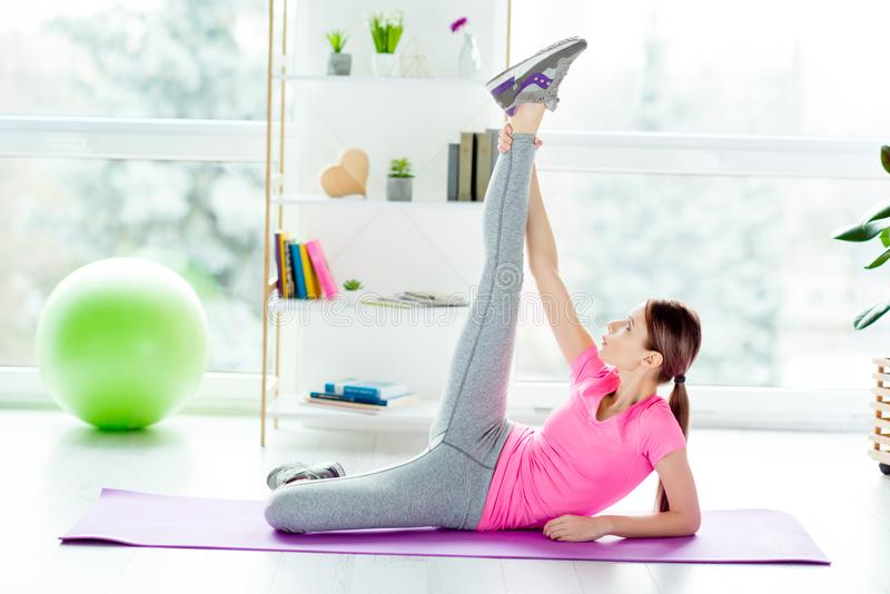 Pretty charming strong cute lovely slim slender flexible woman s. Tretching and warming up her muscles before doing splits holding touching ankle putting leg up stock image