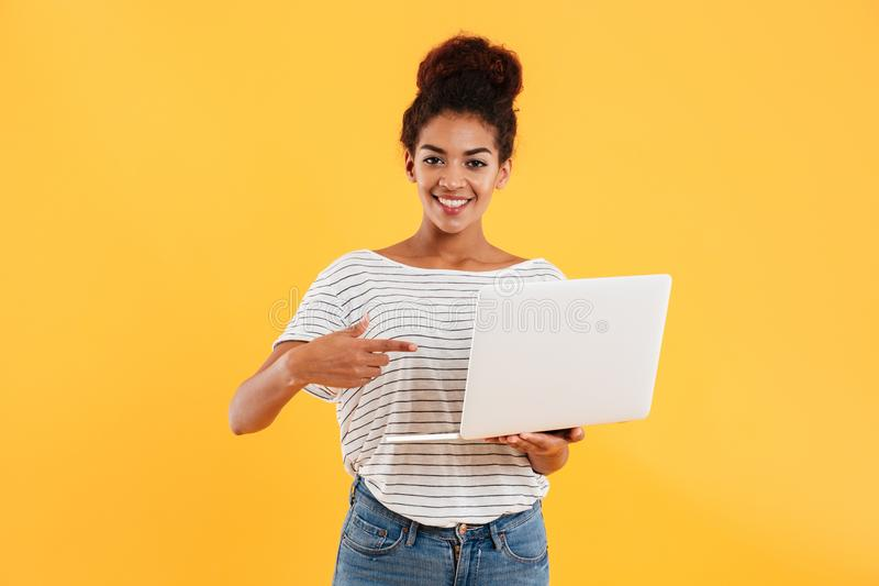 Pretty cheerful african lady looking camera and holding camera isolated. Pretty cheerful african lady ponting and holding laptop computer while looking camera stock photo
