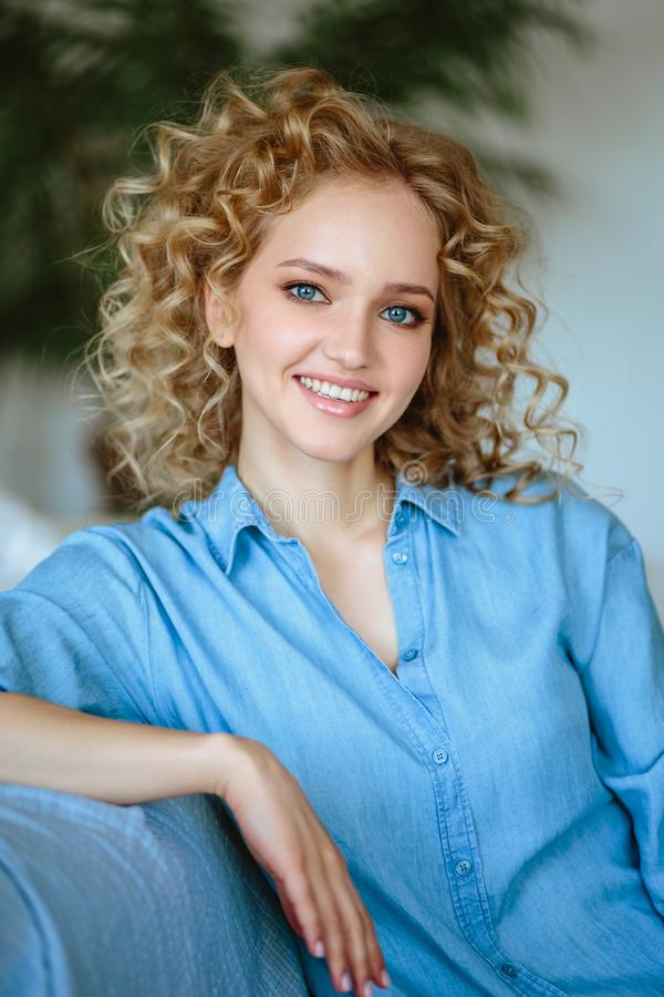 Pretty cheerful blonde young woman with curly hair and charming smile resting in her home. Room with modern scandinavian interior royalty free stock photos