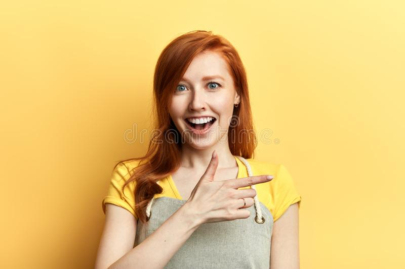 Pretty cheerful positive girl gesturing with fingers, pointing at somewhere royalty free stock photos