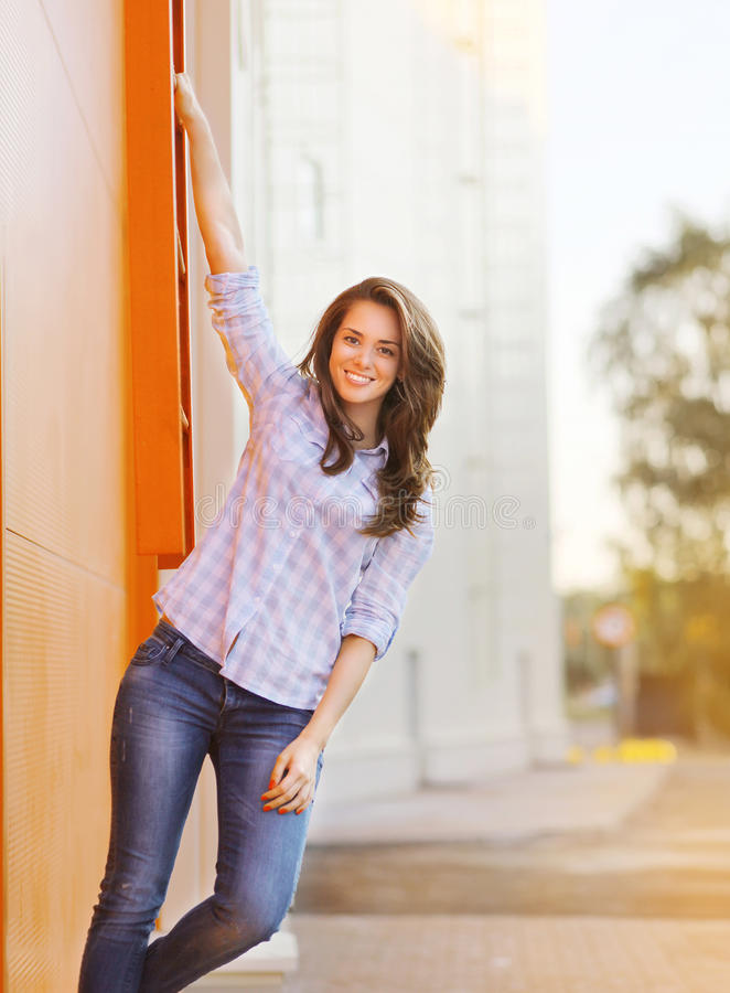 Pretty cheerful woman posing near bright colorful wall royalty free stock photo