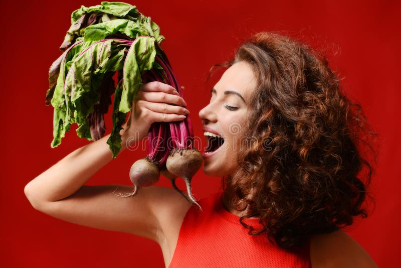 Pretty cheerful young sport woman posing with fresh beetroot green leaves. royalty free stock photography
