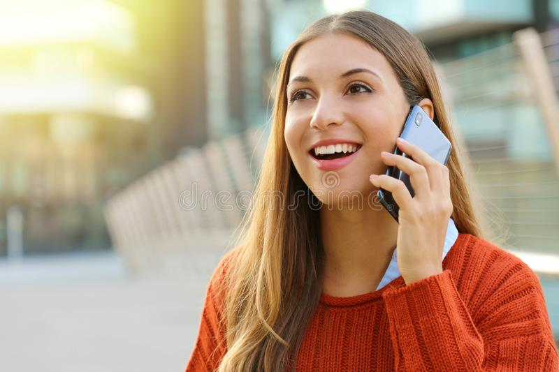 Pretty cheerful young woman talking on phone and looks straight ahead. Girl holding smartphone close to ear standing alone outside royalty free stock photos