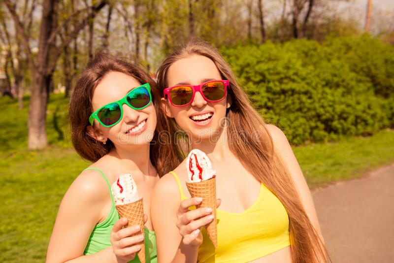 Pretty cheerful young women walking in park with ice cream.  stock photography