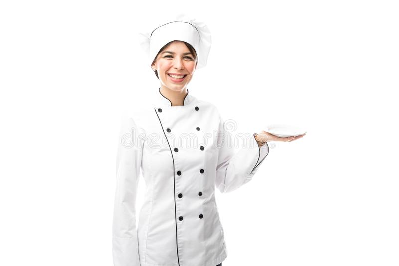 Pretty chef holding an empty plate royalty free stock photos