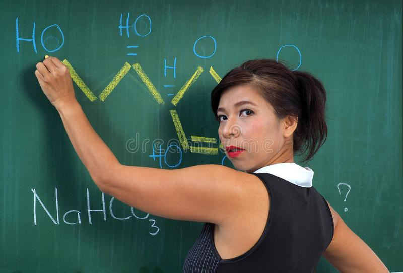 Pretty chemistry teacher writes a structural formula royalty free stock image