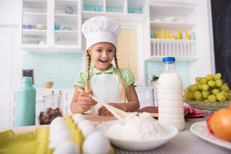 Pretty child cooking with enjoyment royalty free stock photos