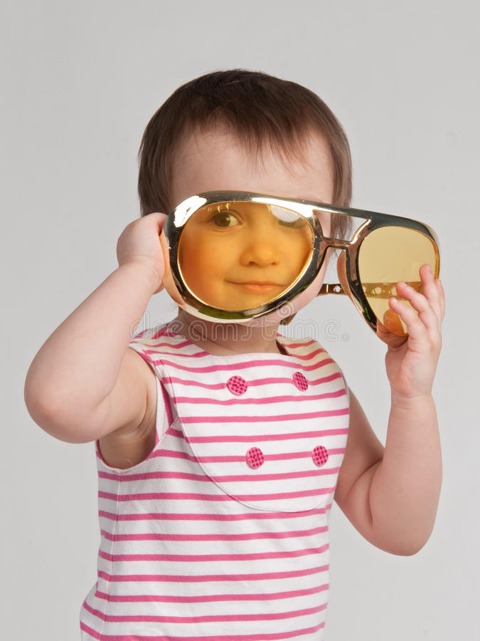 Pretty child with giant sunglasses royalty free stock image