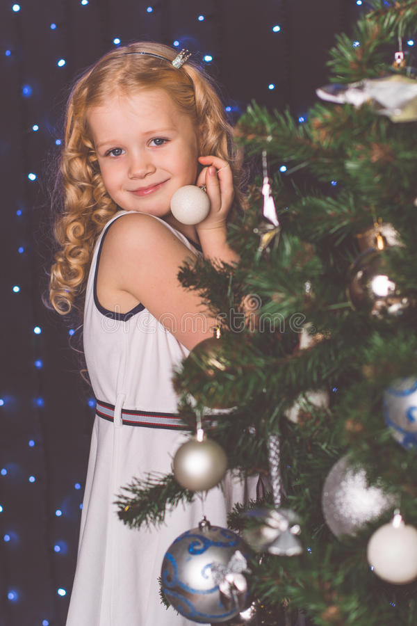 Pretty child girl near decorated christmas tree stock image