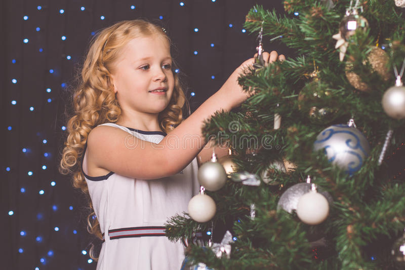 Pretty child girl near decorated christmas tree royalty free stock photography