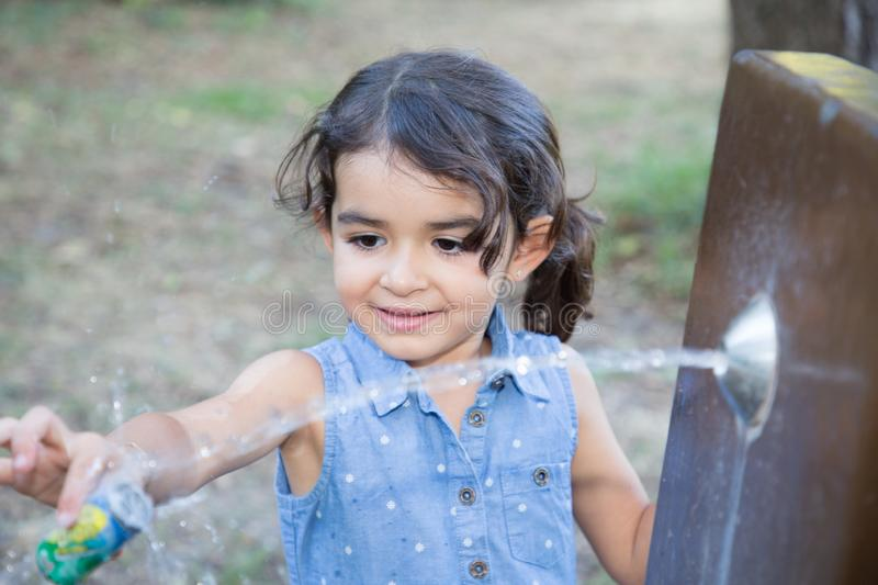Child girl in park play with water fountain. Pretty child girl in park play with water fountain stock photo