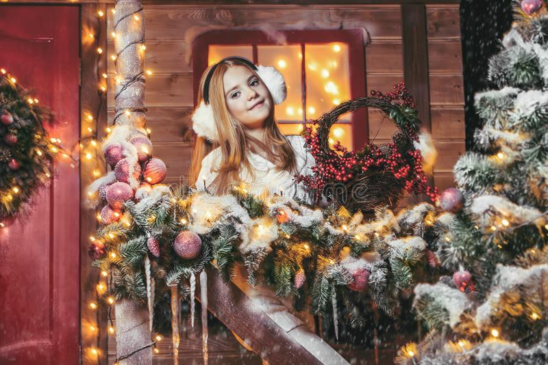 Girl near decorated house. Pretty child girl is standing near her house decorated for Christmas. Merry Christmas and Happy New Year stock photography
