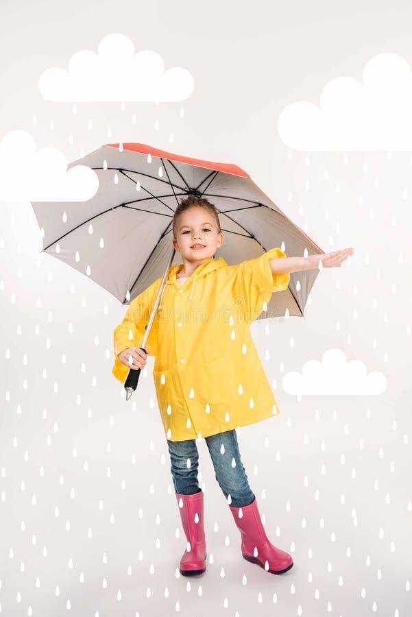 pretty child in rubber boots, yellow raincoat with umbrella, stock image