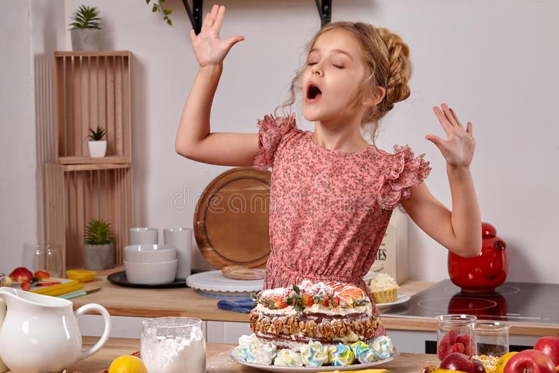 Little girl is making a homemade cake with an easy recipe at kitchen against a white wall with shelves on it. Pretty child wearing in a pink dress is making a stock photo