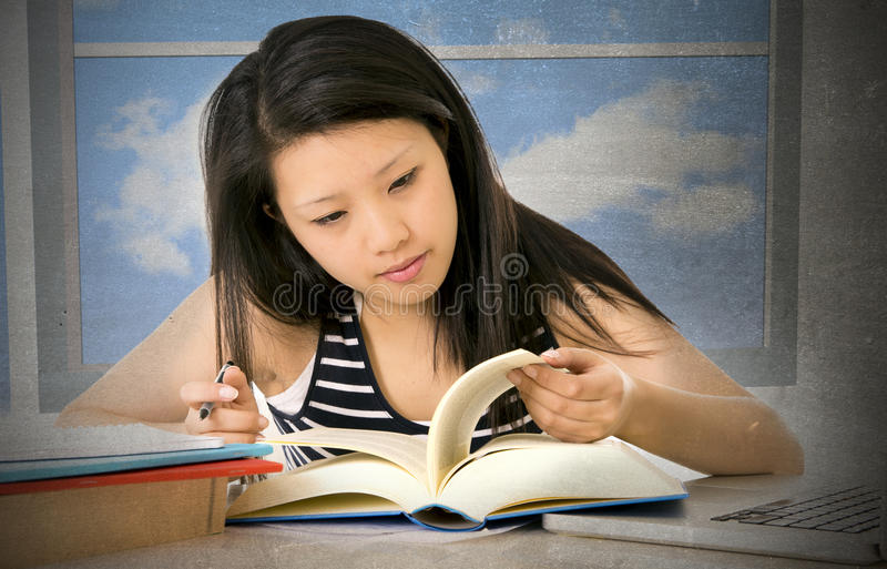 Pretty chinese asian young girl reading and studying with school books and computer laptop at home studio desk stock images