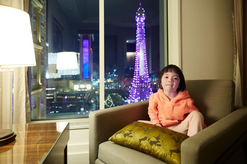 Little girl in hotel room with Eiffel Tower night scene outside. Pretty Chinese baby girl sitting on sofa, Parisian Resort Hotel room with Eiffel Tower night