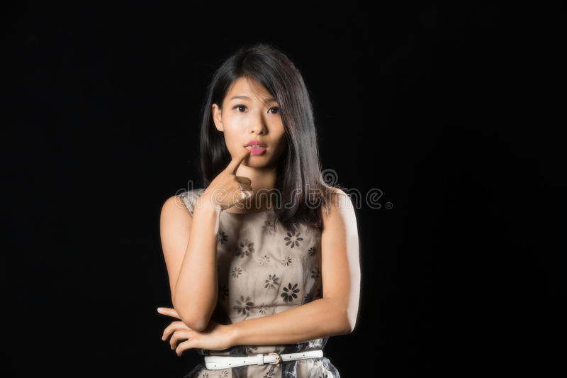 Pretty chinese girl with finger on her lip standing against black background stock photo
