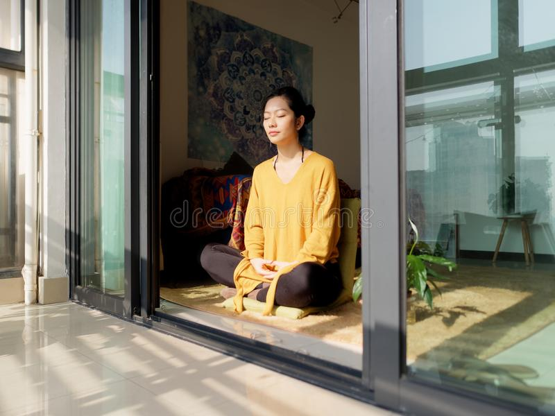 Pretty Chinese young woman meditating at home, sitting on floor with furry cushion in sun light, exercise, Lotus pose, prayer royalty free stock photos