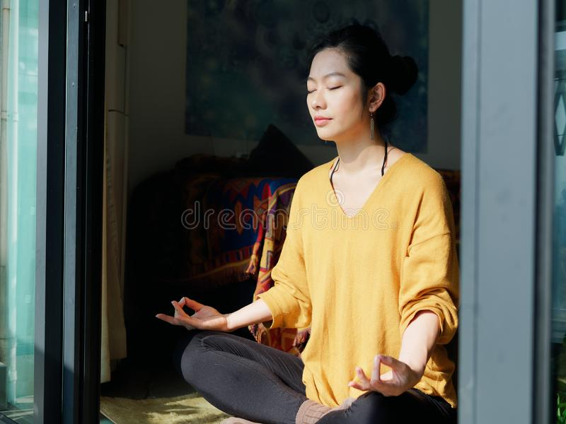 Pretty Chinese young woman meditating at home, sitting on floor with furry cushion in sun light royalty free stock images