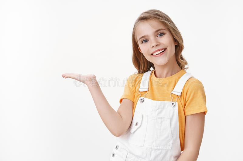 Pretty clever little girl, child with blond hairstyle in yellow t-shirt and overalls hold something on palm, introduce royalty free stock photography