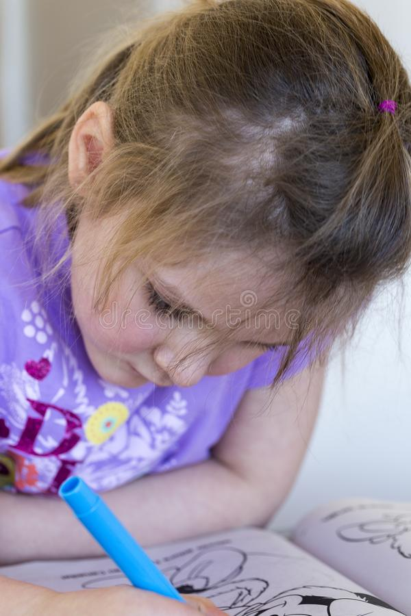 Pretty concentrated little girl in pale purple shirt drawing in book. With blue felt pen royalty free stock photos