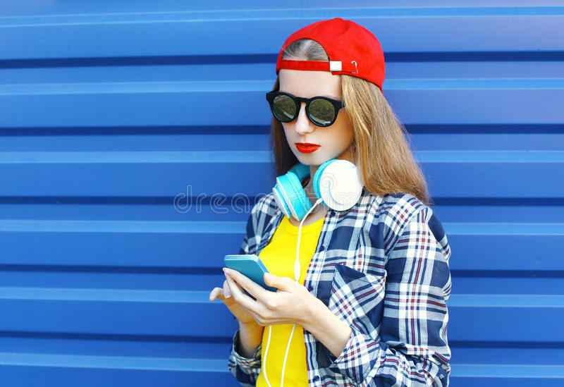 Pretty cool girl listens to music in headphones and using smartphone royalty free stock photo