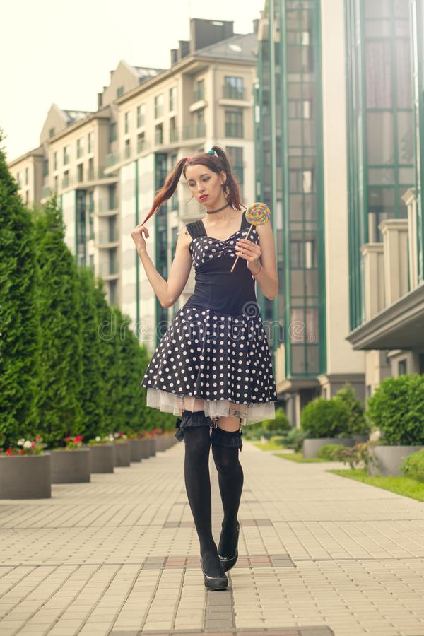 Pretty cosplay girl. Attractive young woman with candy in black dress walking on street stock images