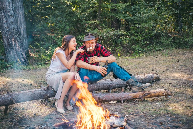 Pretty couple camping with marshmallows over a camp fire. Happy young couple camping in woods. Friends couples enjoy royalty free stock image