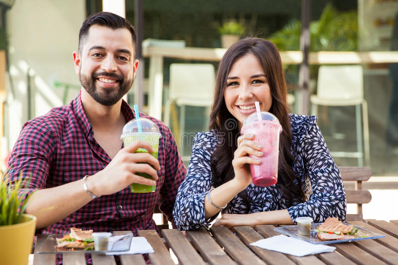Pretty couple drinking smoothies royalty free stock photos