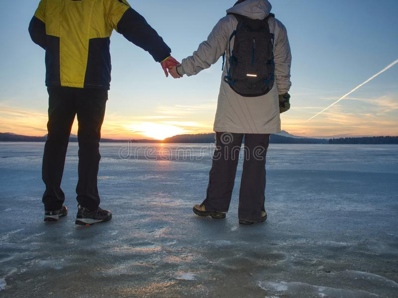 Pretty couple have fun on beach. Winter walk at frozen sea stock photography