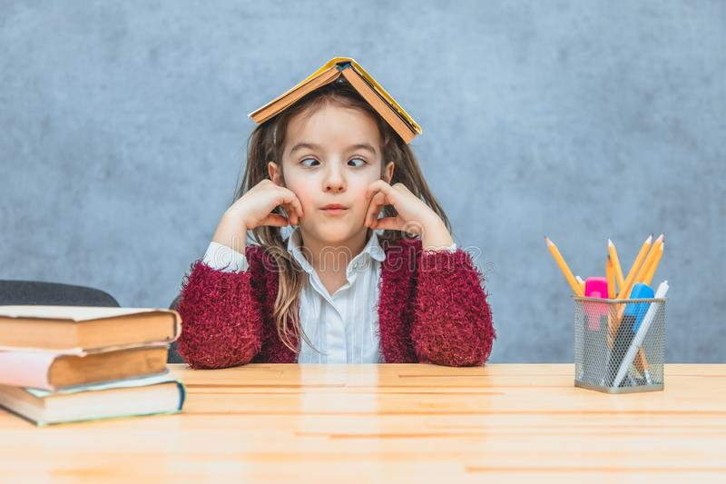 Pretty curly girl sitting and holding a book over her head over a grey background. During this schoolgirl takes her eyes stock photos