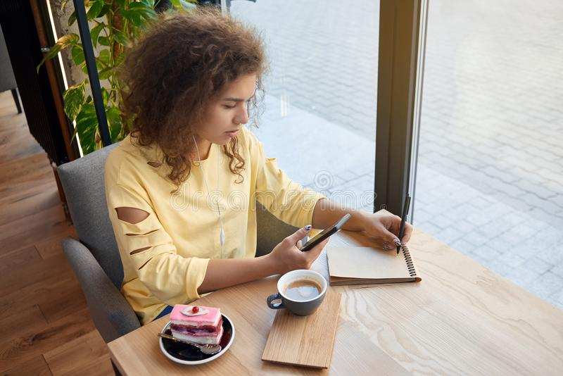 Pretty curly girl writing notes, drinking coffee in caffee. stock images