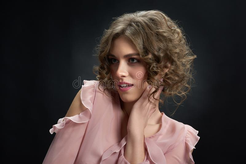 Pretty curly model is posing on dark background. stock images