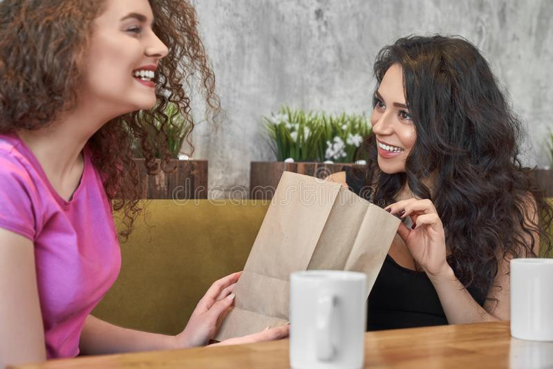 Pretty curly woman making present to female friend in cafe stock images