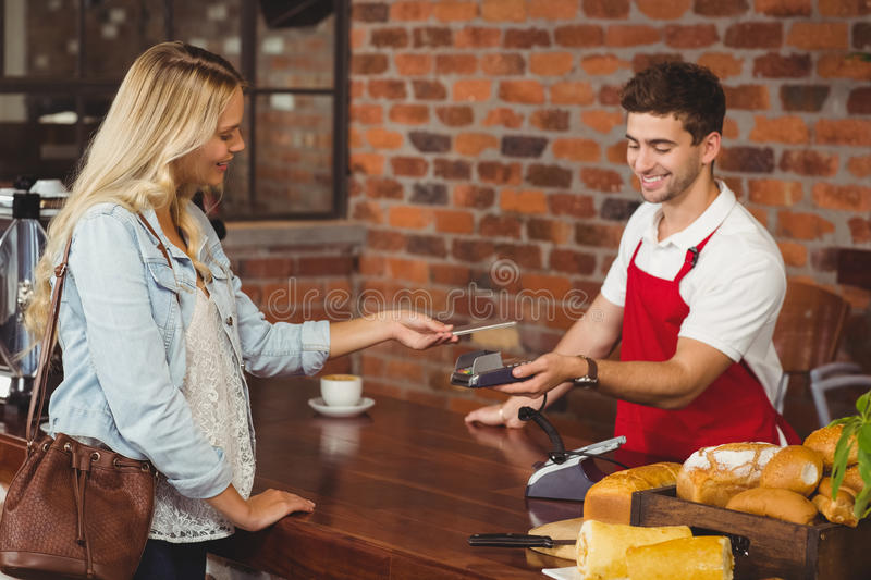 Pretty customer making a mobile payment. At the coffee shop royalty free stock photos