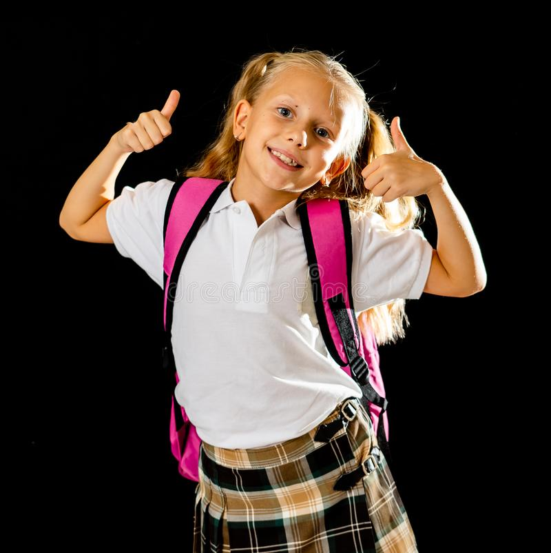 Pretty cute blonde hair girl with a pink schoolbag looking at camera showing thumb up gesture happy to go to school isolated on. Black background in back to stock photos