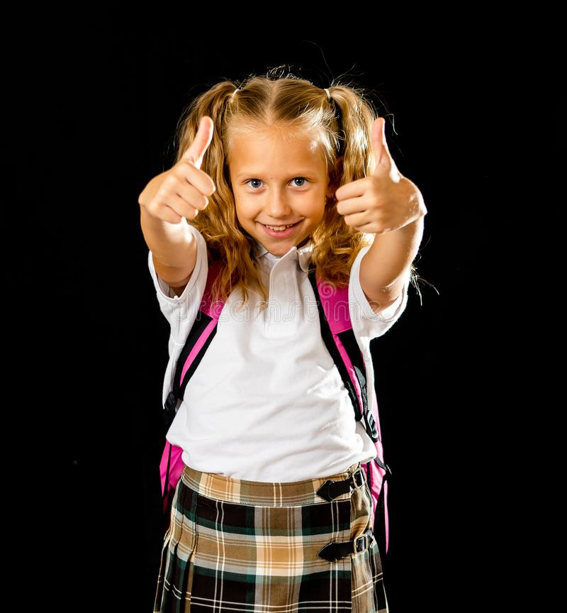 Pretty cute blonde hair girl with a pink schoolbag looking at camera showing thumb up gesture happy to go to school isolated on royalty free stock image