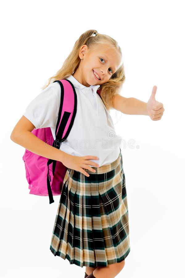 Pretty cute blonde hair girl with a pink schoolbag looking at camera showing thumb up gesture happy to go to school isolated on. White background in back to stock photos