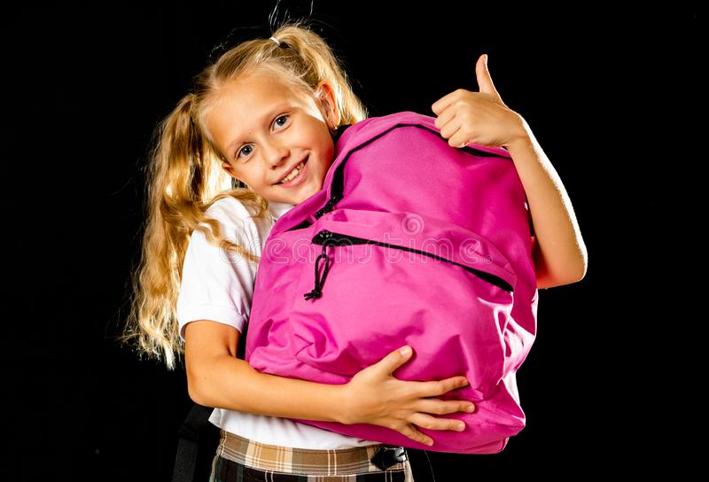 Pretty cute blonde hair girl with a pink schoolbag looking at camera showing thumb up gesture happy to go to school isolated on. White background in back to royalty free stock photography
