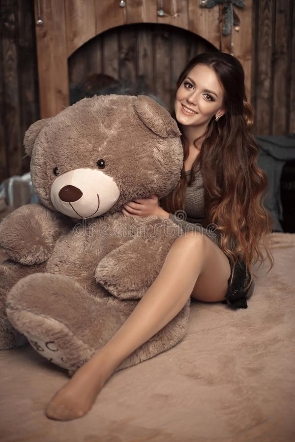 Pretty cute brunette girl posing with big teddy bear on the floor in cozy comfortable interior home. stock image