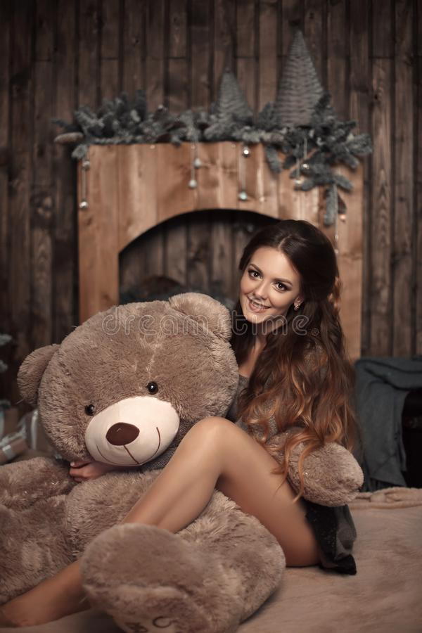 Pretty cute brunette girl posing with big teddy bear on the floor in cozy comfortable interior home. royalty free stock images