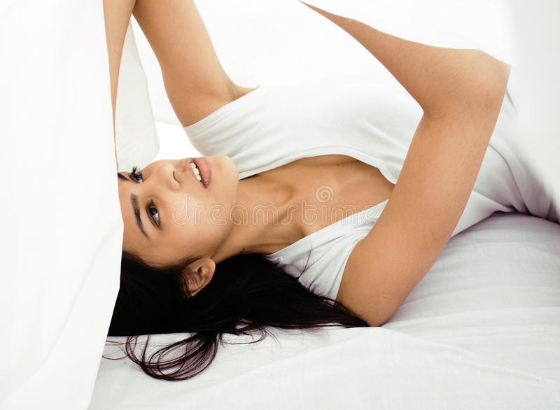 Pretty Cute Brunette Woman In Bed Under Sheets Royalty Free Stock Image