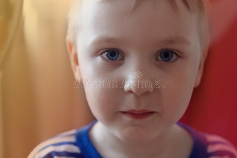 Pretty cute caucasian baby boy with bright blue eyes looks to the camera. Strong emotions, serious face expression. Portrait of beautiful child on bright stock photo