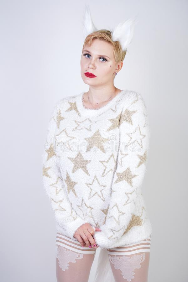 Pretty cute kind girl with blonde short hair and curvy plus size body wearing white sweater with golden stars and fluffy fur cat e stock image