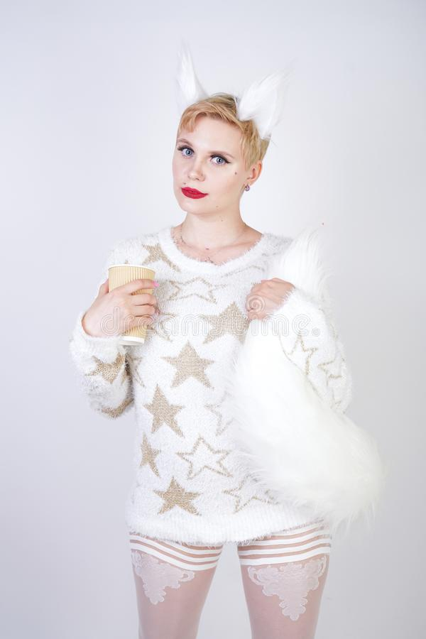 Pretty cute kind girl with blonde short hair and curvy plus size body wearing white sweater with golden stars and fluffy fur cat e royalty free stock photography