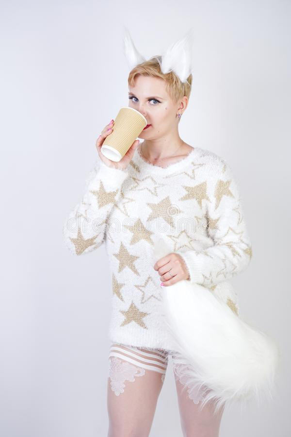 Pretty cute kind girl with blonde short hair and curvy plus size body wearing white sweater with golden stars and fluffy fur cat e stock images