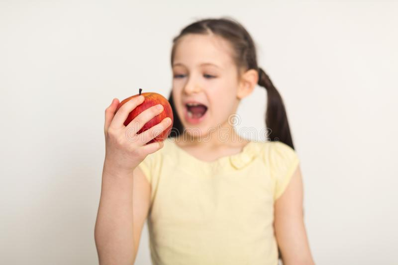 Pretty cute little girl biting red apple over white background royalty free stock photos