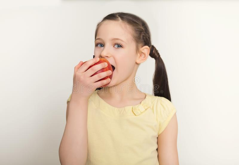 Pretty cute little girl biting red apple over white background stock photography